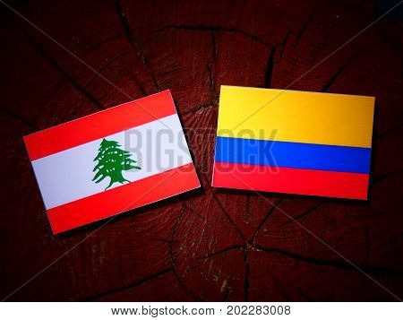 Lebanese Flag With Colombian Flag On A Tree Stump Isolated