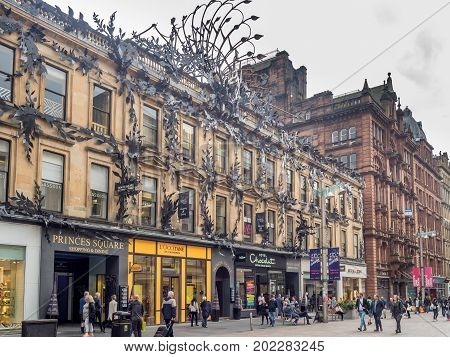 GLASGOW, SCOTLAND - JULY 21: Shops and people on Buchanan Street on July 21, 2017 in Glasgow, Scotland. Buchanan is the main shopping district in Scotland and has many fine restaurants and shops.