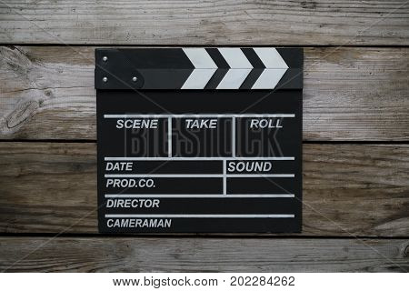 movie clapper on wood table ; film cinema and video photography concept