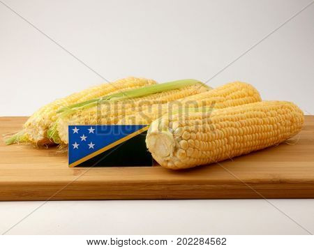 Solomon Islands Flag On A Wooden Panel With Corn Isolated On A White Background