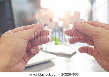 Young businessman trying to connect couple puzzle piece with sun flare and blur backgroundsymbol of association and connection. business strategy.