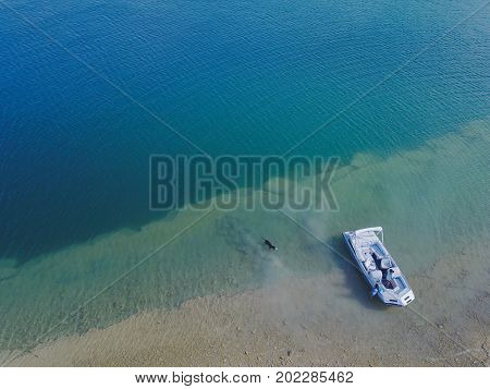 beautiful blue lake with a boat from arial view