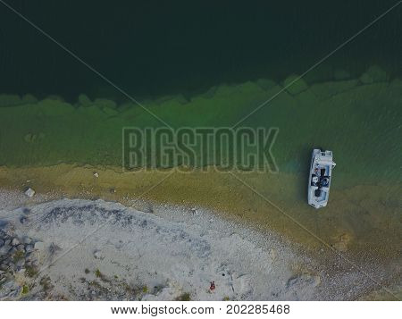 arial view of a clear lake, shore and boat