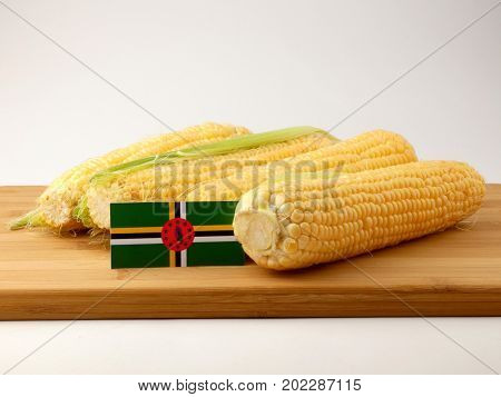 Dominica Flag On A Wooden Panel With Corn Isolated On A White Background