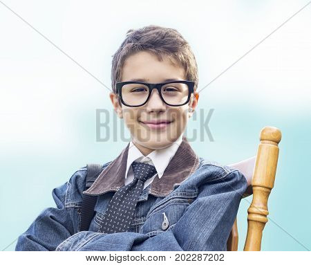 Smart Preteen Boy With Black Eye Glasses Sitting In Chair With Arms Crossed, Denim Jacket, Tie And B