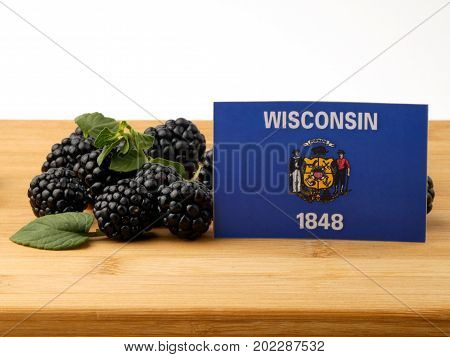 Wisconsin Flag On A Wooden Panel With Blackberries Isolated On A White Background