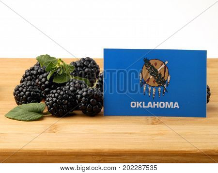 Oklahoma Flag On A Wooden Panel With Blackberries Isolated On A White Background