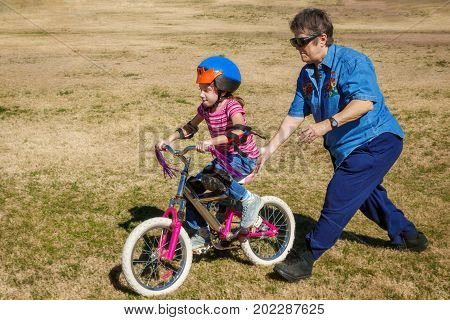A grandmother pushes her granddaughter on a bicycle as she learns to ride. The girl is wearing a helmet and pads. They are on mostly dead grass. Grandma has dark sunglasses.