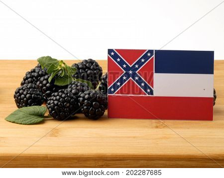 Mississippi Flag On A Wooden Panel With Blackberries Isolated On A White Background