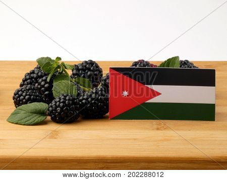 Jordanian Flag On A Wooden Panel With Blackberries Isolated On A White Background