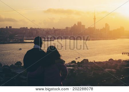 Happy senior couple watching sunset in Auckland city skyline with city center and Auckland Sky Tower in New Zealand.