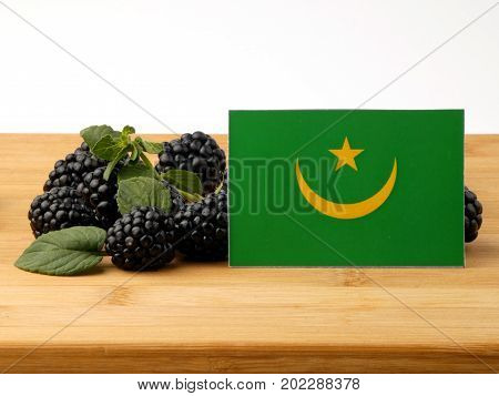 Mauritania Flag On A Wooden Panel With Blackberries Isolated On A White Background