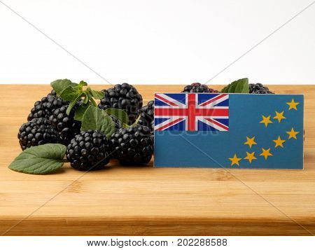 Tuvalu Flag On A Wooden Panel With Blackberries Isolated On A White Background
