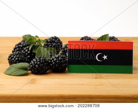 Libyan Flag On A Wooden Panel With Blackberries Isolated On A White Background