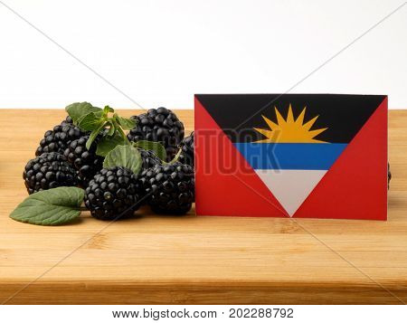 Antigua And Barbuda Flag On A Wooden Panel With Blackberries Isolated On A White Background