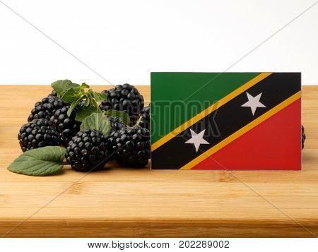 Saint Kitts And Nevis Flag On A Wooden Panel With Blackberries Isolated On A White Background
