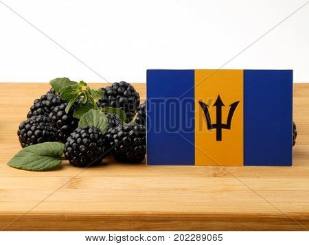 Barbados Flag On A Wooden Panel With Blackberries Isolated On A White Background