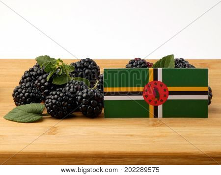 Dominica Flag On A Wooden Panel With Blackberries Isolated On A White Background