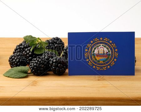 New Hampshire Flag On A Wooden Panel With Blackberries Isolated On A White Background