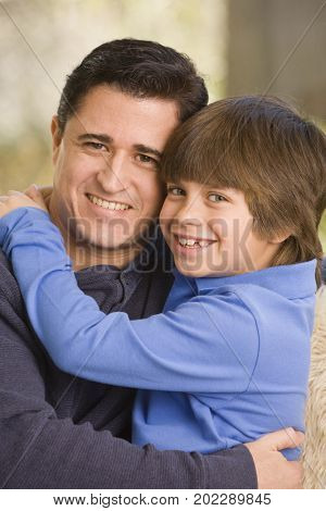 Hispanic father and son hugging