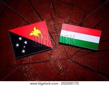 Papua New Guinea Flag With Hungarian Flag On A Tree Stump Isolated