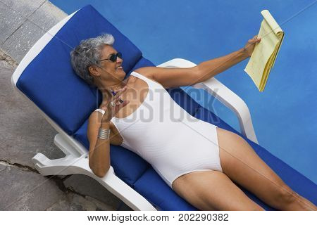 Senior Hispanic woman holding notebook next to swimming pool