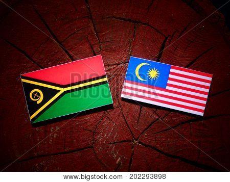 Vanuatu Flag With Malaysian Flag On A Tree Stump Isolated