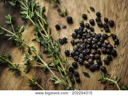 Aerial view of fresh thyme and black peppercorns herb on wooden table