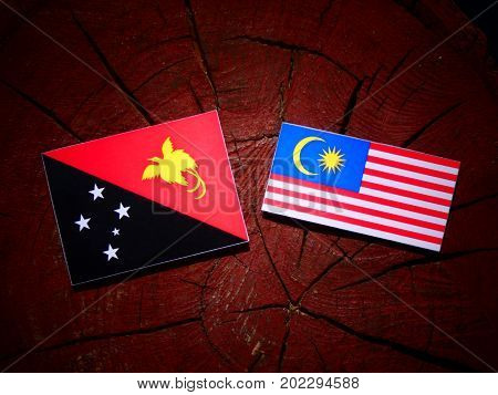 Papua New Guinea Flag With Malaysian Flag On A Tree Stump Isolated