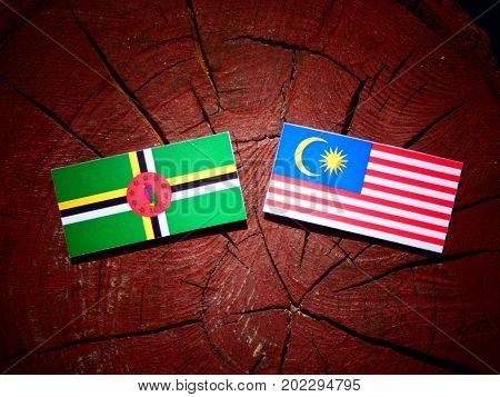 Dominica Flag With Malaysian Flag On A Tree Stump Isolated