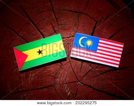 Sao Tome And Principe Flag With Malaysian Flag On A Tree Stump Isolated