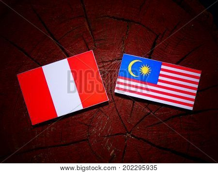Peruvian Flag With Malaysian Flag On A Tree Stump Isolated