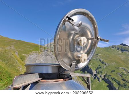 close on a vat opening of a milk can in front of mountain