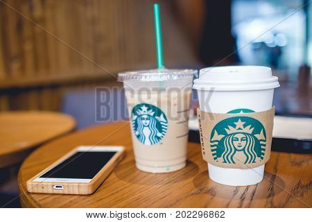 Bangkok Thailand - Aug 30 2017: Hot and cold coffee and smartphone on wooden table in Starbucks coffee shop. Selective focus