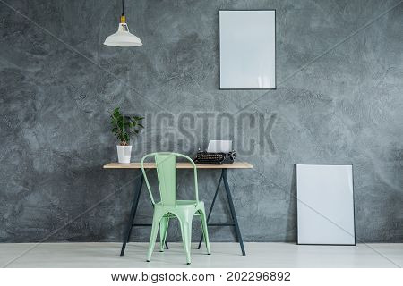 Small lampshade hanging above desk with green chair