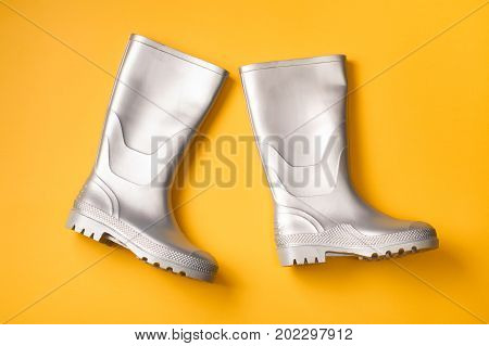 From above view of trendy silver rain boots on orange background. Top view. Flat lay.