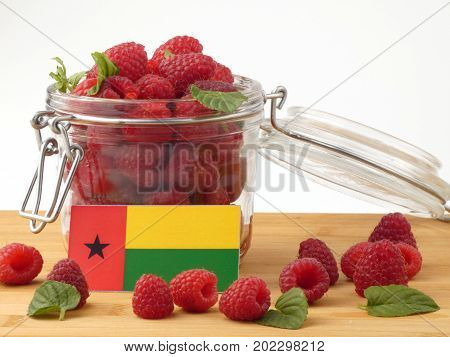 Guinea Bissau Flag On A Wooden Panel With Raspberries Isolated On A White Background