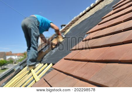 new tiles on a roof with a roofer working background