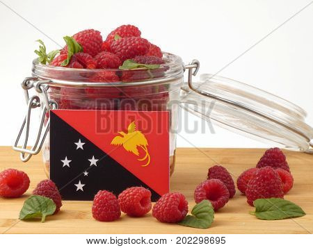 Papua New Guinea Flag On A Wooden Panel With Raspberries Isolated On A White Background