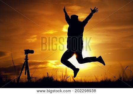 Silhouette of female photographing herself with photo camera and tripod at the background of setting sun. Happy woman jumping and raising hands to the sky. Travelling and tourism concept.