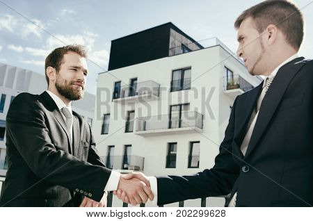 Two Men Are Standing On The Balcony And Shaking Hands.