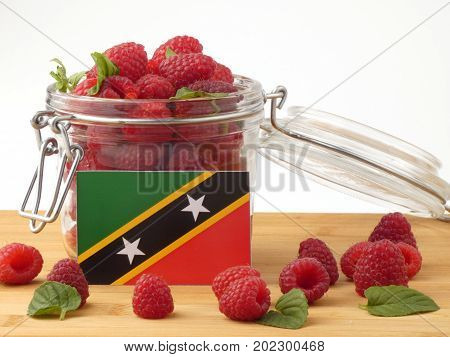 Saint Kitts And Nevis Flag On A Wooden Panel With Raspberries Isolated On A White Background