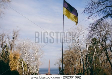 Ukrainian Blue-yellow Flag Flutters In The Wind Against The Background Of The Sea And A Monument To