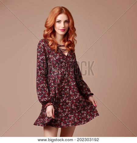 Fall Fashion. Model Woman in Autumn Outfit. Redhead in Stylish Floral Dress, Trendy Curly Hairstyle. Fashion autumn Lady. Glamour Playful Sexy Girl, Fashion Pose. Fall Concept. Vintage