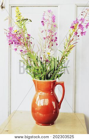 Bunch of wildflowers in the jug on a background of the white door