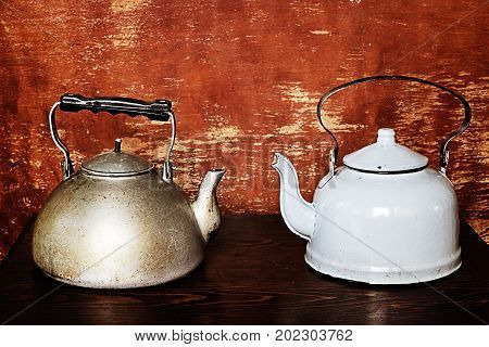 Two old kettles on the wooden background