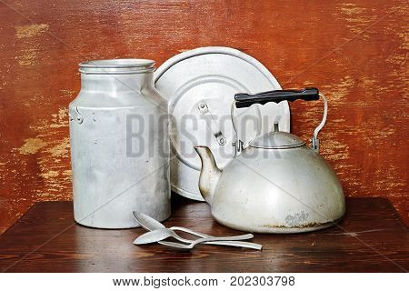 Vintage cooking crockery are a kettle, milk can, spoons