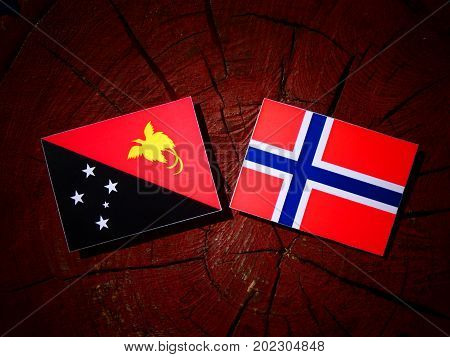 Papua New Guinea Flag With Norwegian Flag On A Tree Stump Isolated