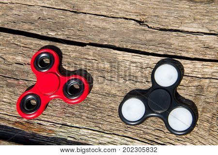 Two Fidget Spinners On Wooden Table