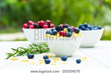 A useful breakfast with fresh berries. Corn flakes and ripe berries.